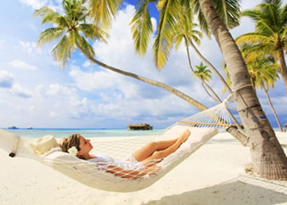 Woman relaxing in a hammock on the beach - for information on sedation dentistry