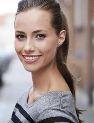 Brunette woman with a long ponytail smiling; for information on Baton Rouge affordable dentistry