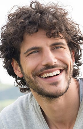 Curly-haire d brunette man with a beard smiling, perhaps after seeing a cater-to-cowards dentist