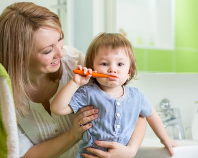 Home bathroom scene of mother teaching a toddler how to brush their teeth.