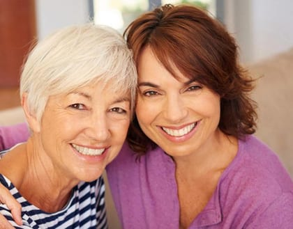 A senior and a middle-aged woman smiling - for information on dentures from Theriot Family Dental Care of Baton Rouge