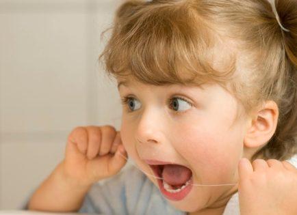 Little girl flossing teeth