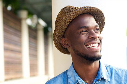 African American man outdoors, smiling, and wearing a straw hat, perhaps after seeing a dentle dentist