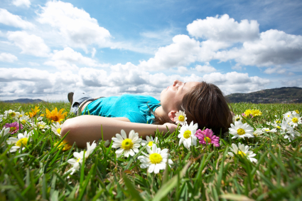 Young woman lying in a field of daisies, as an example of how sleep dentistry is relaxing